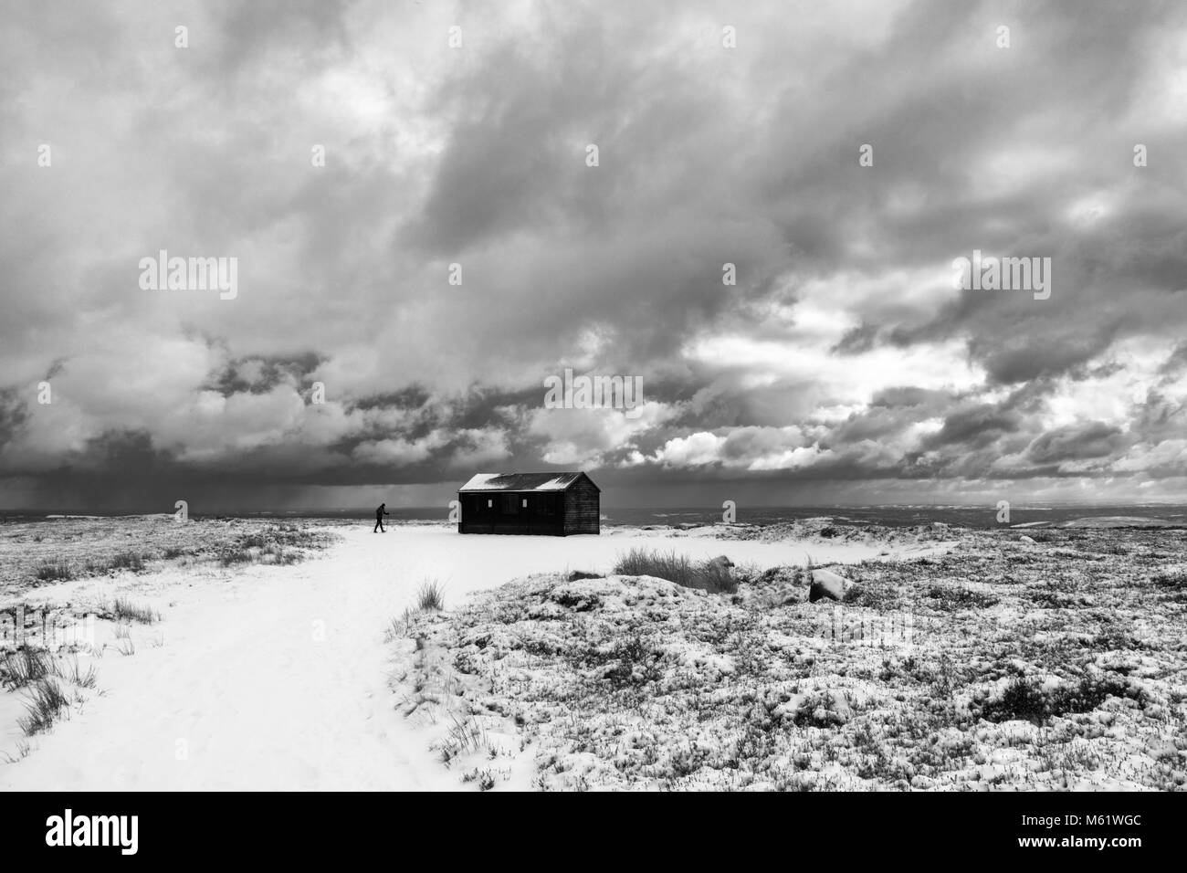 monochrome image of a man walking alone on the moors on a snowy day with a dramatic sky - Stock Image