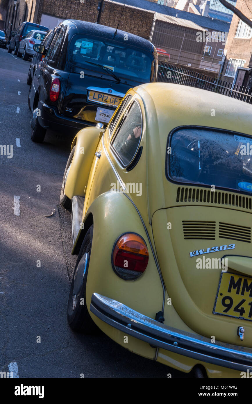 A Volkswagen Beetle original yellow coloured car next to a black cab london taxi in a back street in the capital. Stock Photo