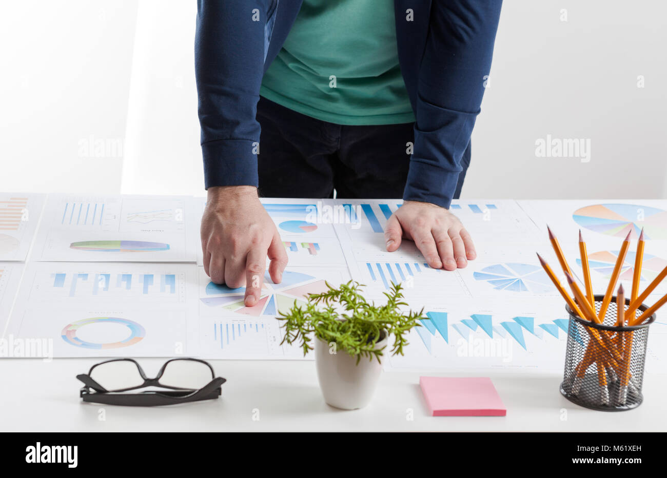 stock market chart and finger pointing on tablet in office - Stock Image