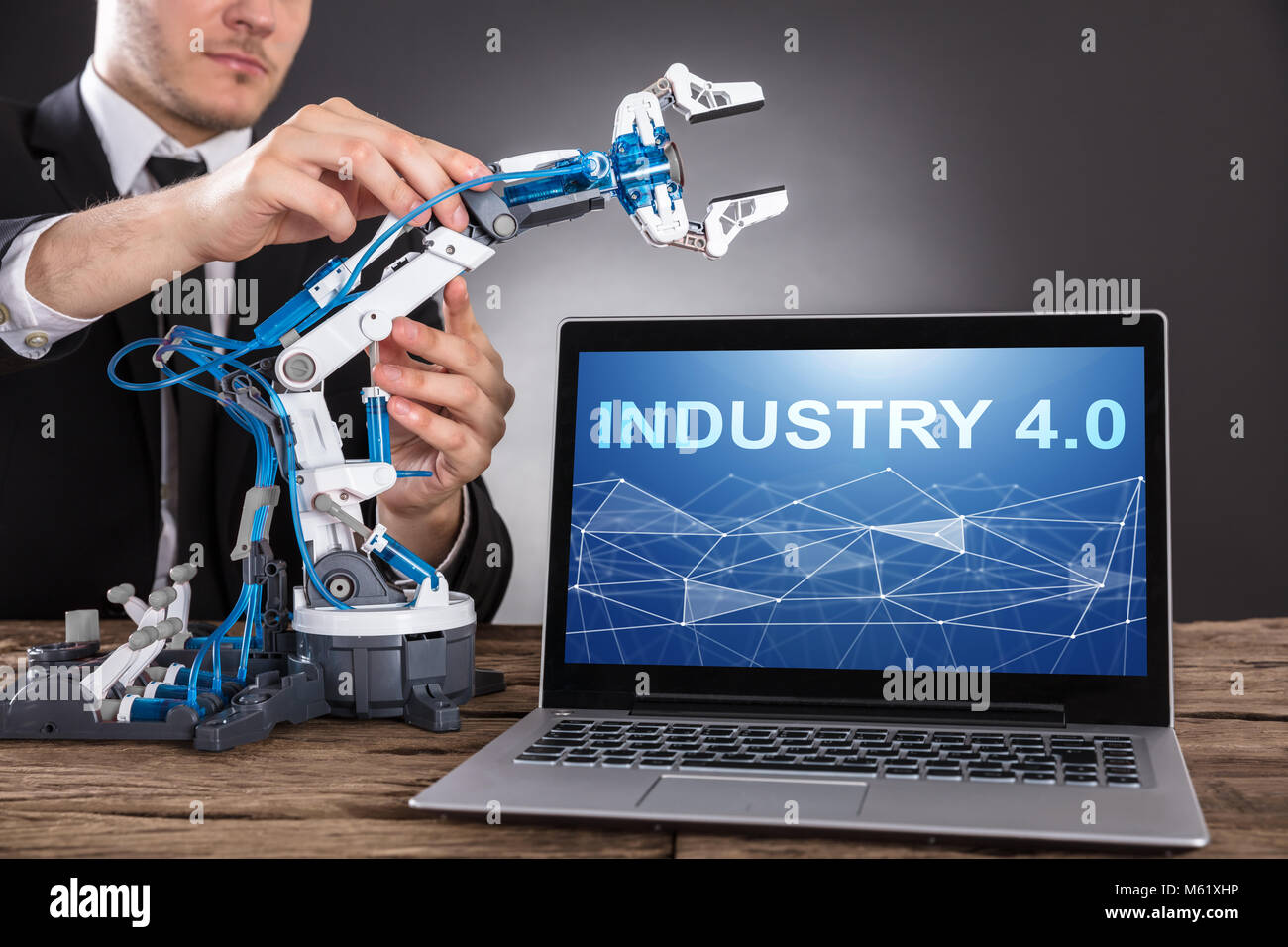 Close-up Of Businessman Building Robot With Laptop Screen Showing Industry 4.0 - Stock Image