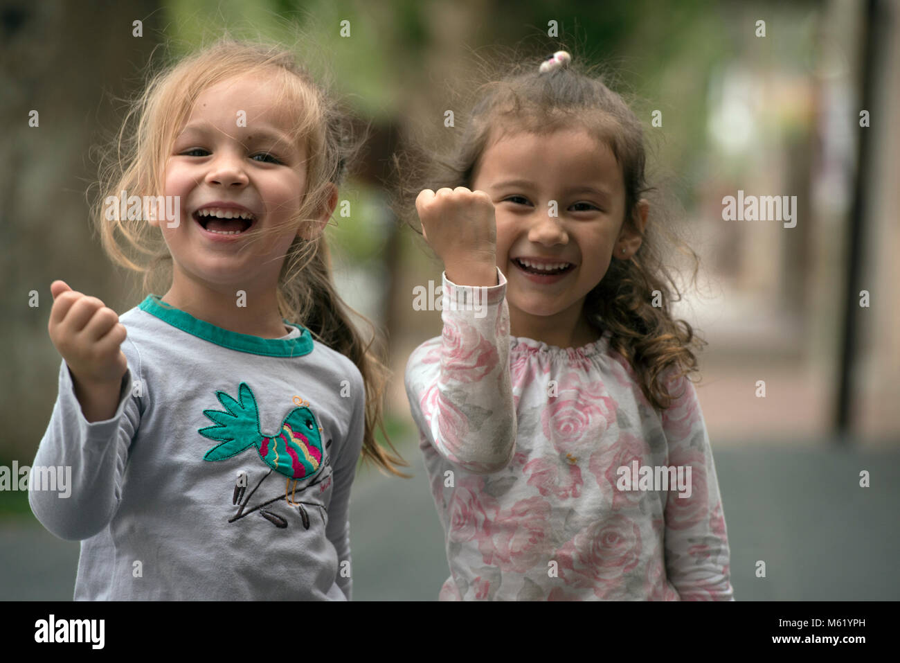 Two young girls pretending to be tough while laughing and smiling. Cafayate, Salta Province, Argentina. - Stock Image