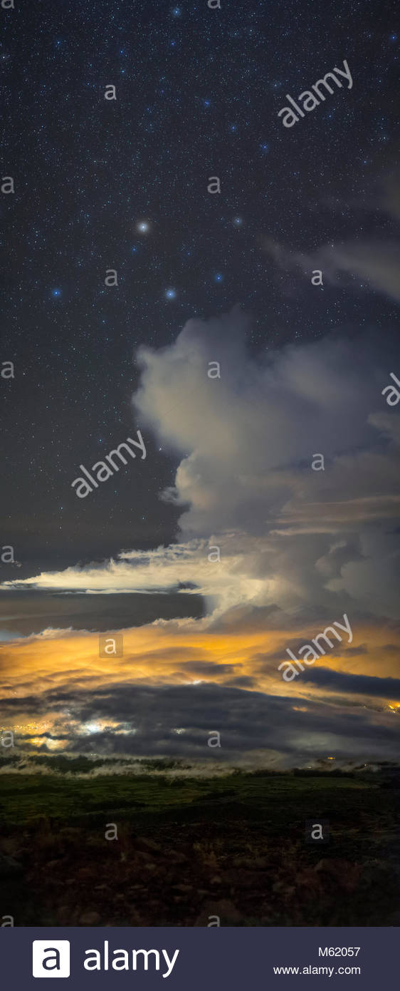 A towering cumulus cloud lit by a town forms a face under stars of constellation Draco. - Stock Image