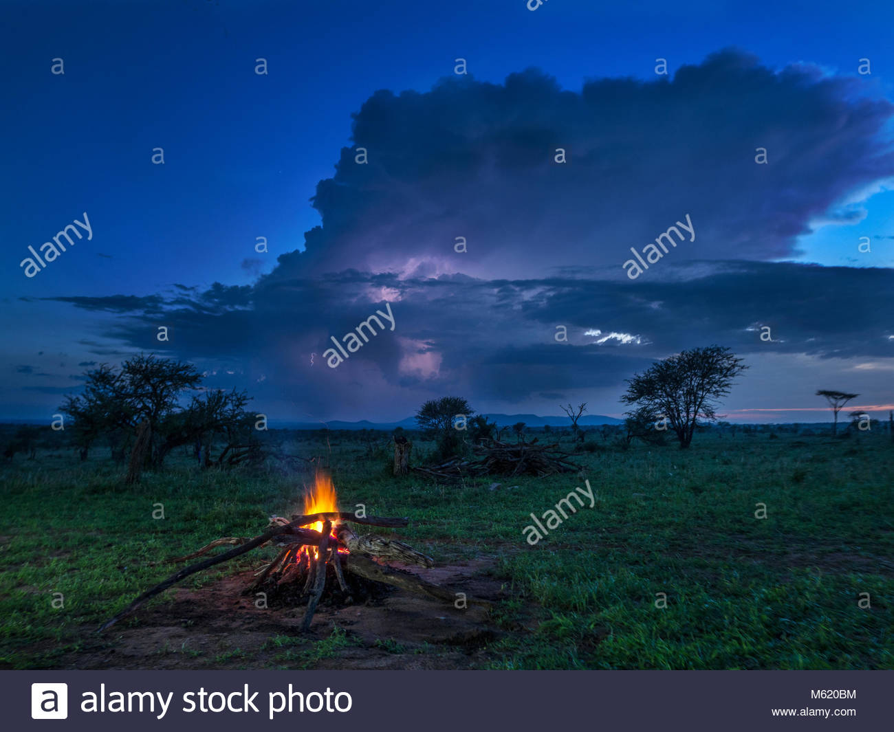 A campfire burns in early evening with storm behind. - Stock Image