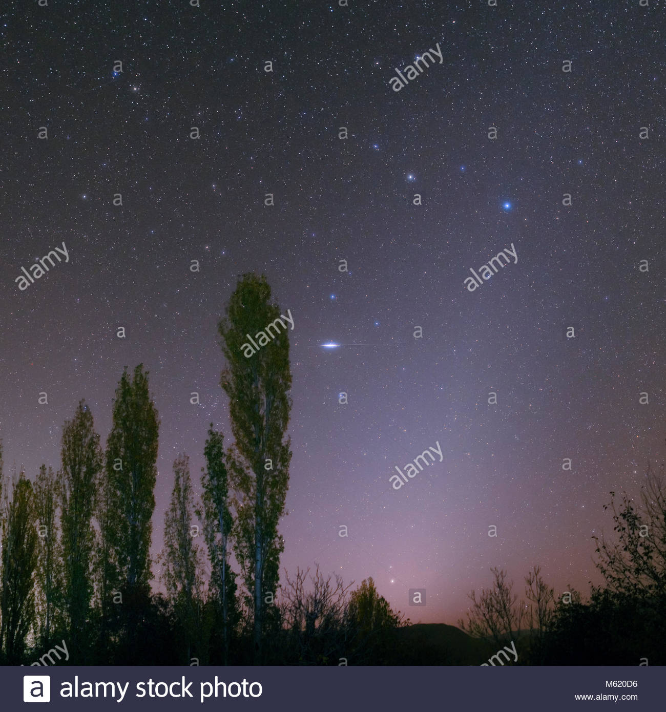 Constellation Leo and the zodiacal light in early morning sky with a bright Iridium satellite. Stock Photo