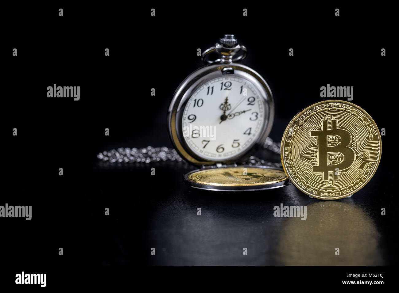 Single golden bitcoin and pocket watch on black background - Stock Image