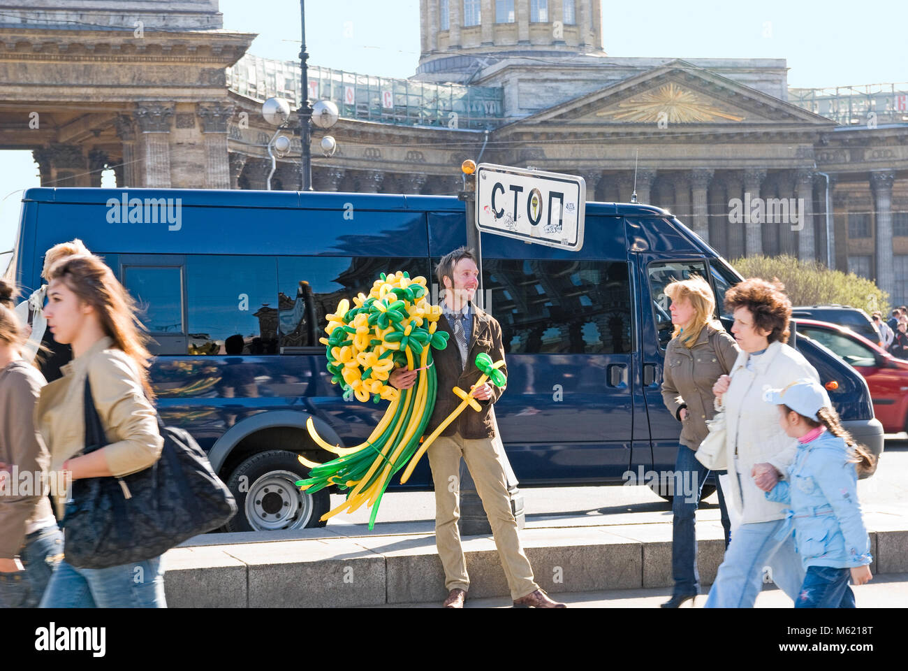 """SAINT-PETERSBURG, RUSSIA, MAY 14, 2011: A smiling young man sells balloon flowers under the sign """"Stop"""" on Nevsky Stock Photo"""