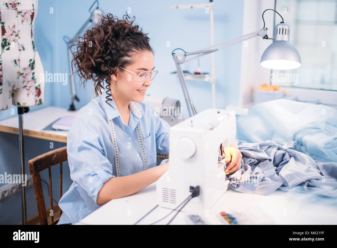 tailor wearing blue blouse and having flexible ruler on her shoulders - Stock Image