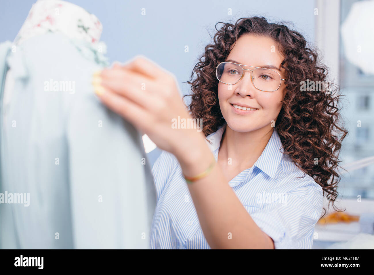 dressmaker in glasses working with dummy. learning how to work with dummy - Stock Image