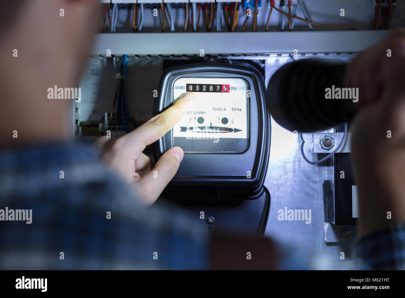 Person's Finger Pointing To Electric Meter Reading Using Flash Light - Stock Image
