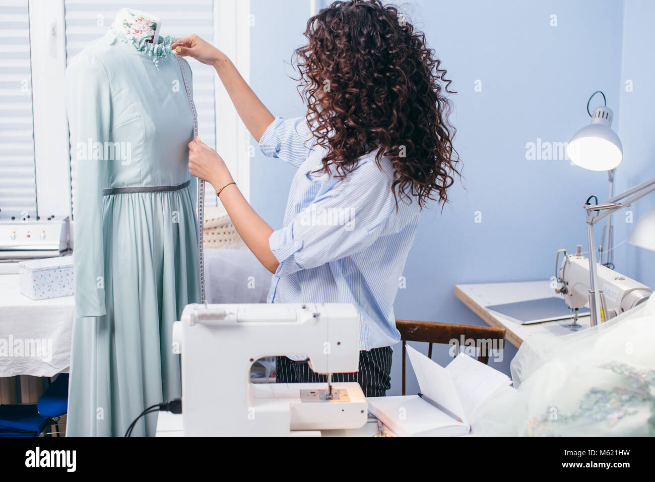 process of measuring accuralty measuring garment on tailor's dummy - Stock Image