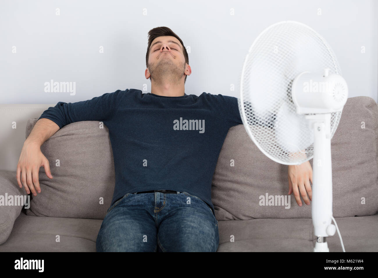 Young Man Sitting On Couch Cooling Off With Fan During Hot Weather At Home - Stock Image