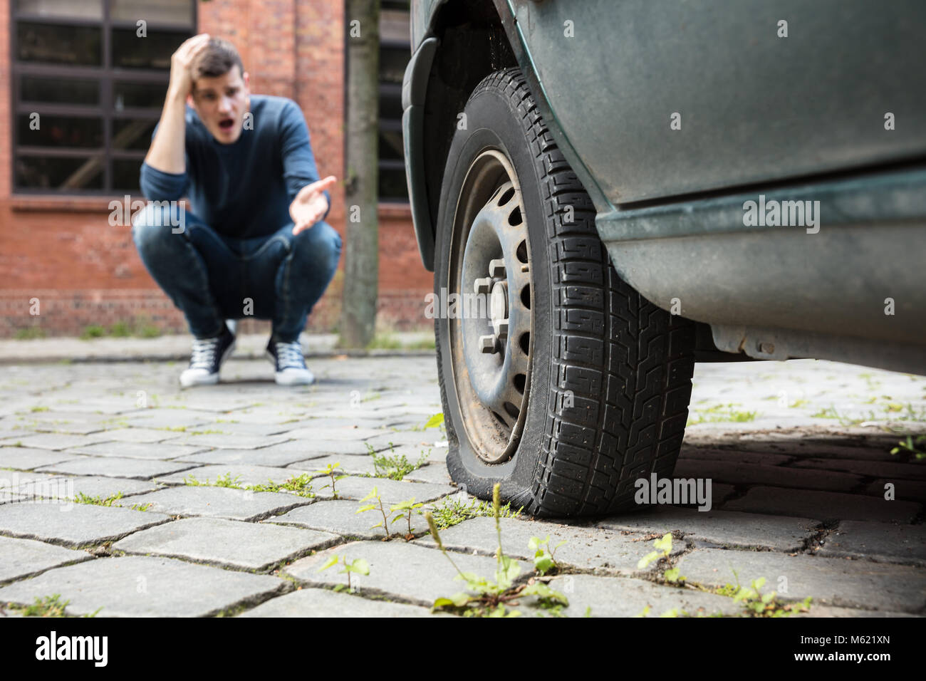 Crouched Worried Young Man With Hand On Head Pointing At Punctured Car Tire - Stock Image