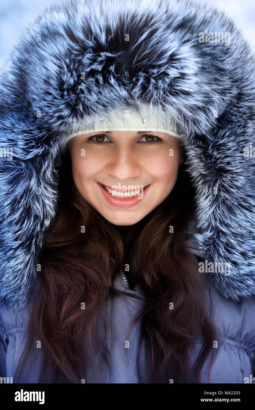 d18eebacd2502 Portrait of a beautiful winter woman in fur hat is walking in the park -  Stock