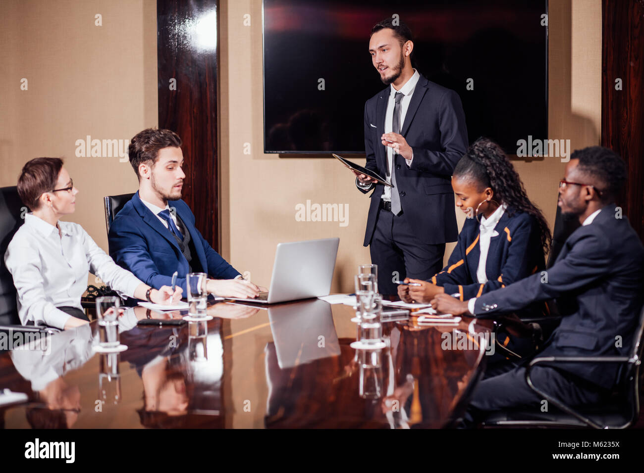 Businessman presenting to colleagues at a meeting - Stock Image