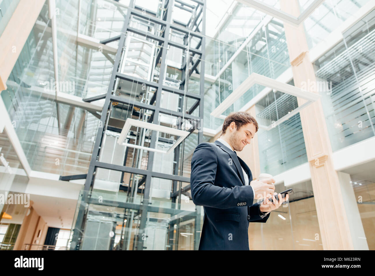 confident man holding coffee cup and using his smart phone while walking in hall Stock Photo