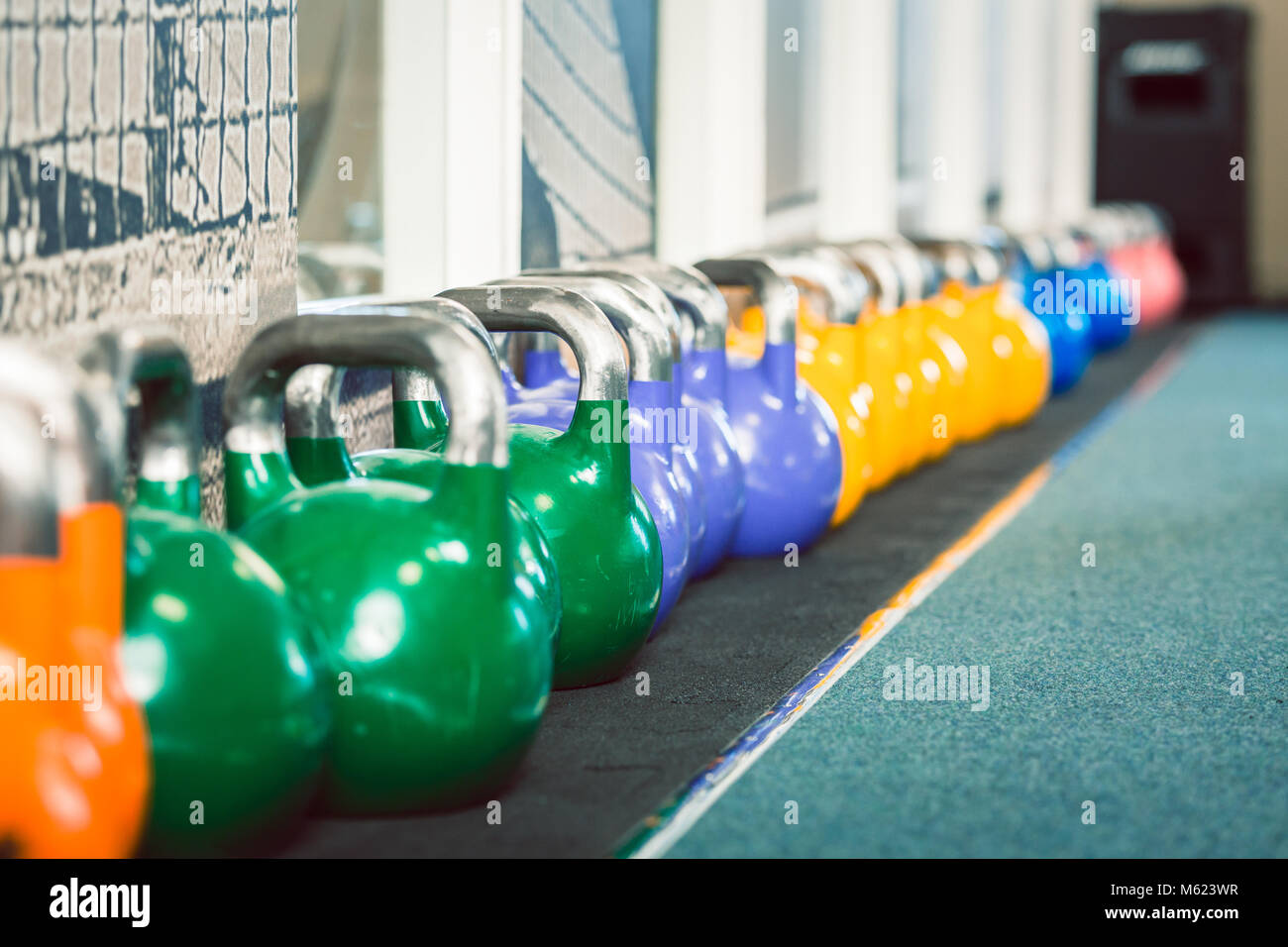 Close-up of kettlebells of various weights and colors - Stock Image