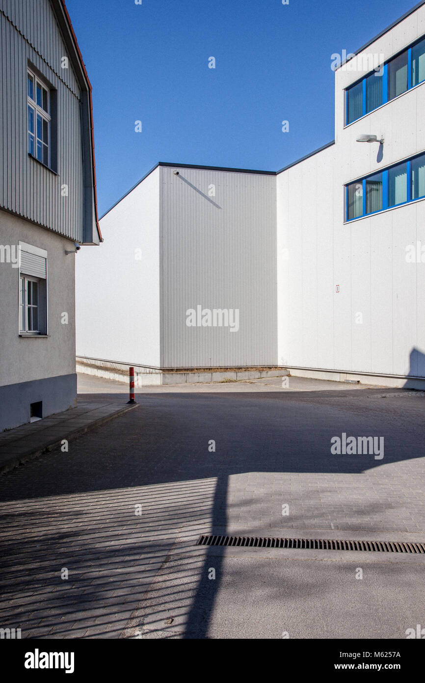 Slip road between an old and a new trade building. - Stock Image