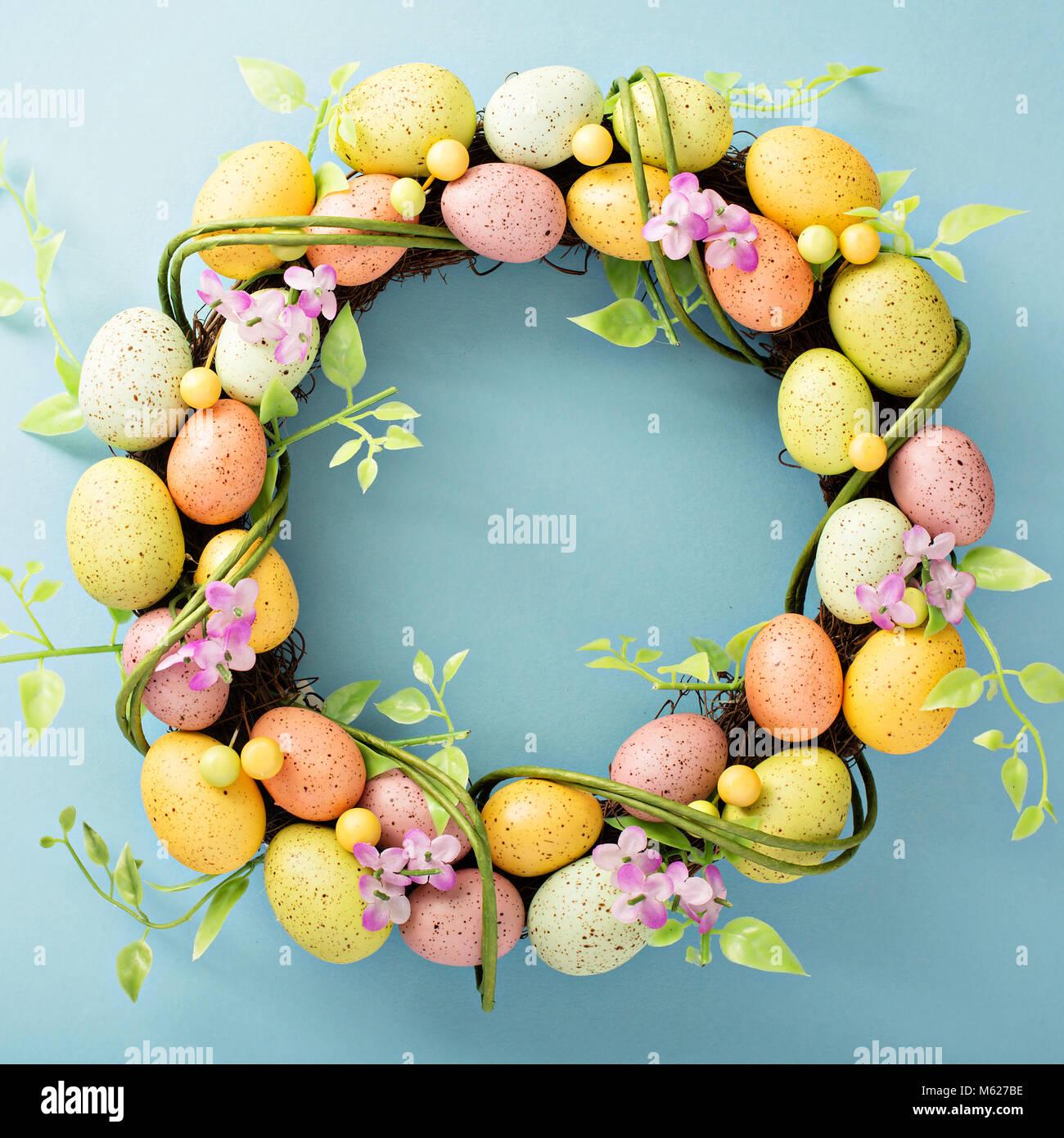 Easter eggs wreath on light blue background - Stock Image