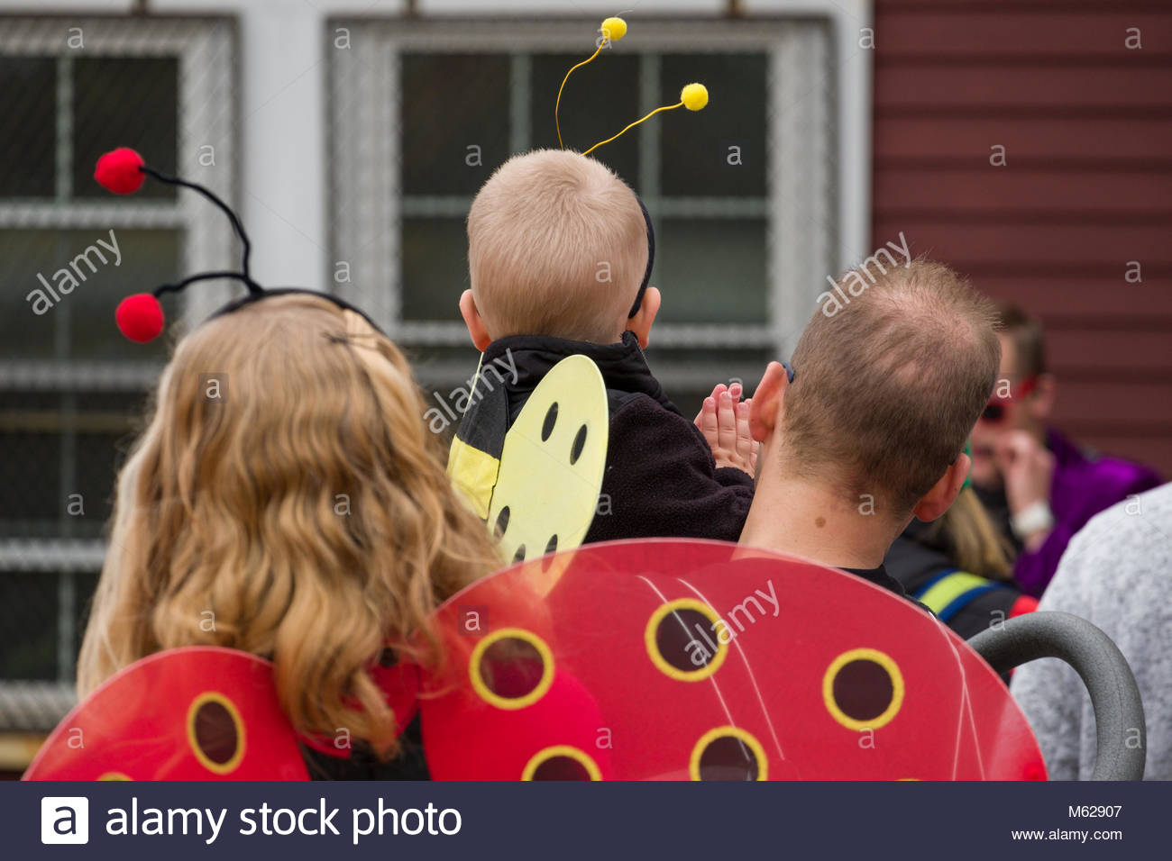 Man holding boy wearing a bug costume with fuzzy antenna on his head at the Ogunquit Village School waiting for - Stock Image
