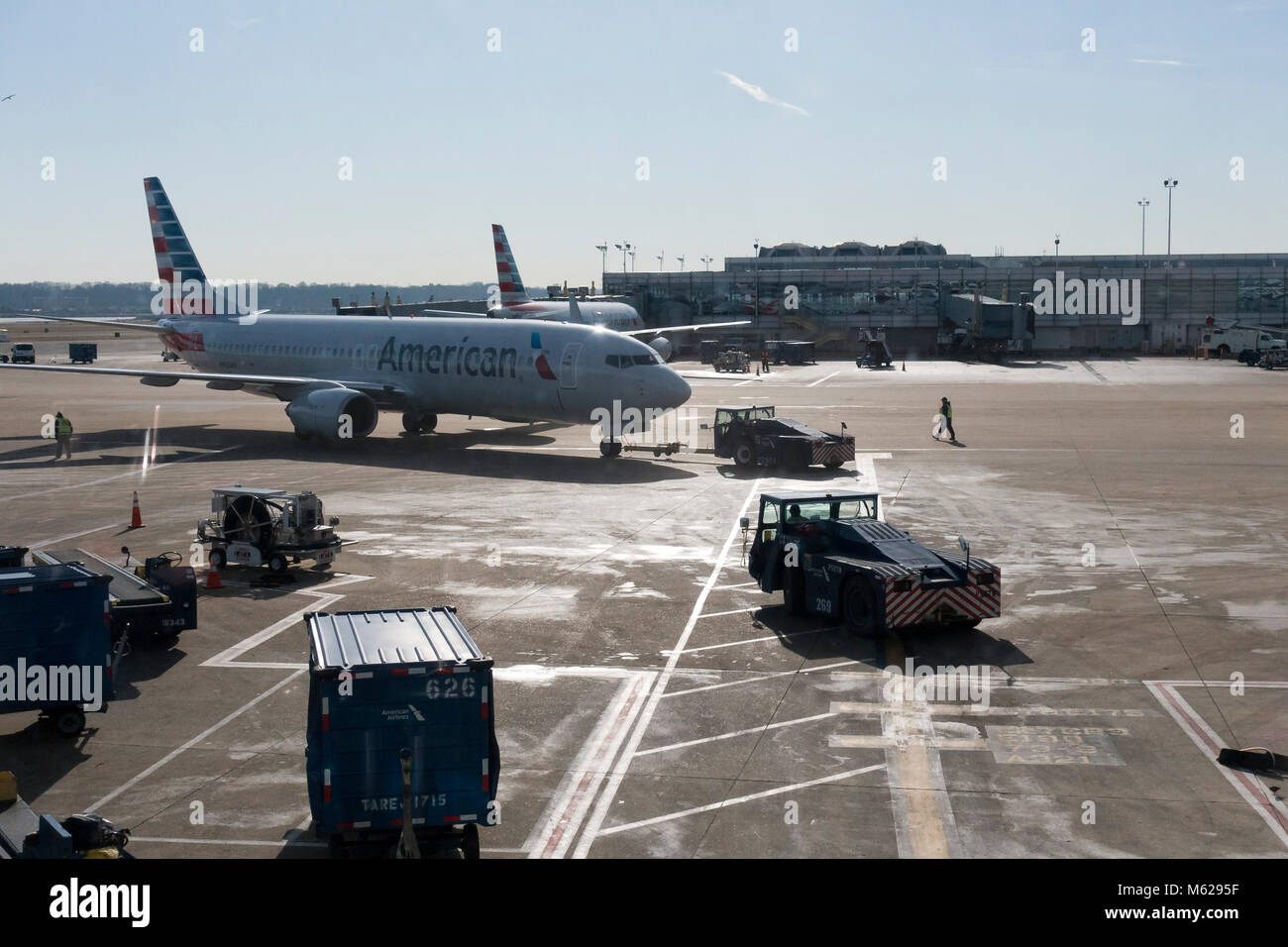 A pushback tractor (pushback tug) preparing to tow an American Airlines Boeing 737 Next Gen (Boeing 737NG) to its - Stock Image