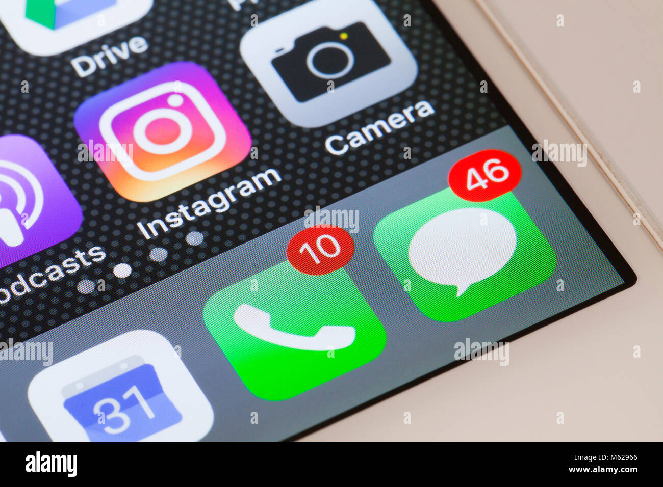 Notification badges (red dot) showing high number of missed calls and text messages on iPhone 5s home screen - USA - Stock Image