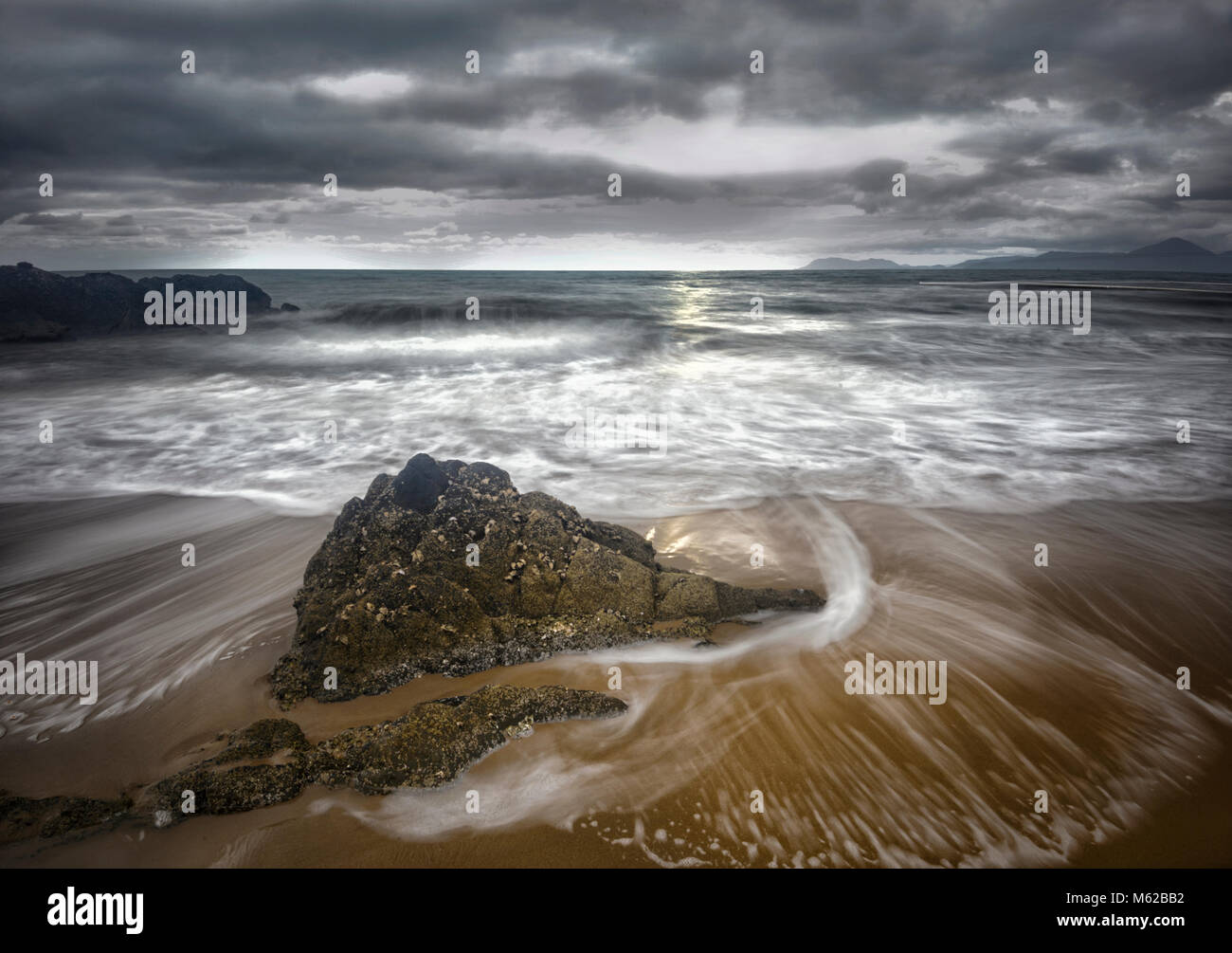 Waves motion blur around a rock at Yorkeys Knob Beach during a storm, Cairns Northern Beaches, Far North Queensland, - Stock Image