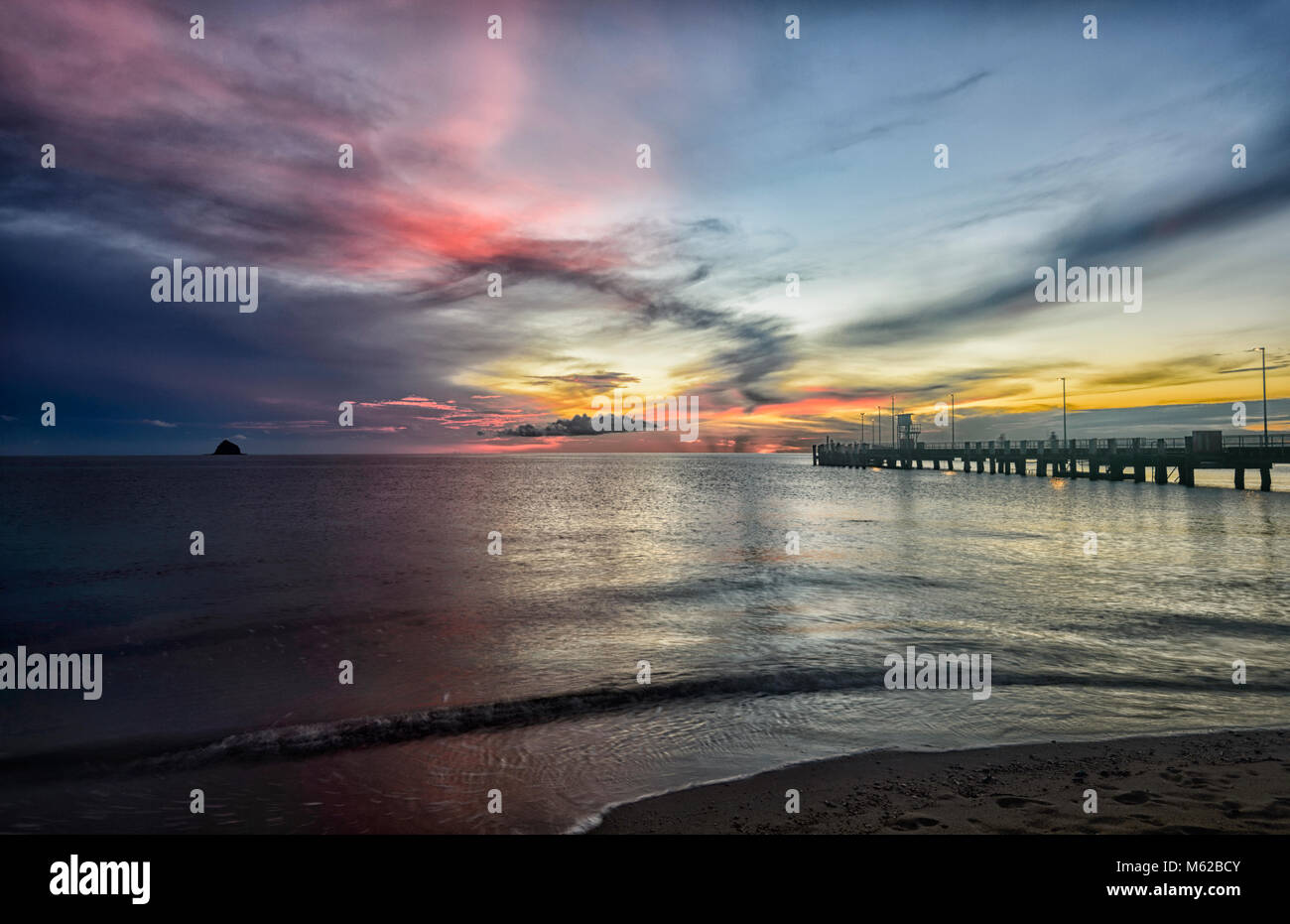Dramatic fiery sunrise by the jetty at Palm Cove Beach, Cairns Northern Beaches, Far North Queensland, FNQ, QLD, - Stock Image