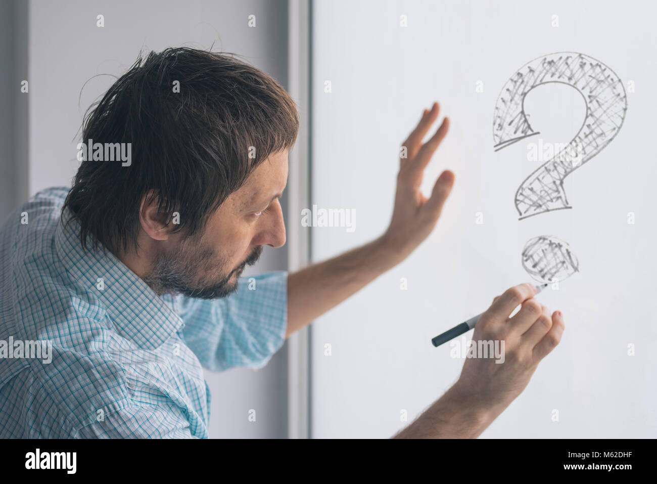 Perplexed businessman drawing question marks on whiteboard in the office, selective focus - Stock Image