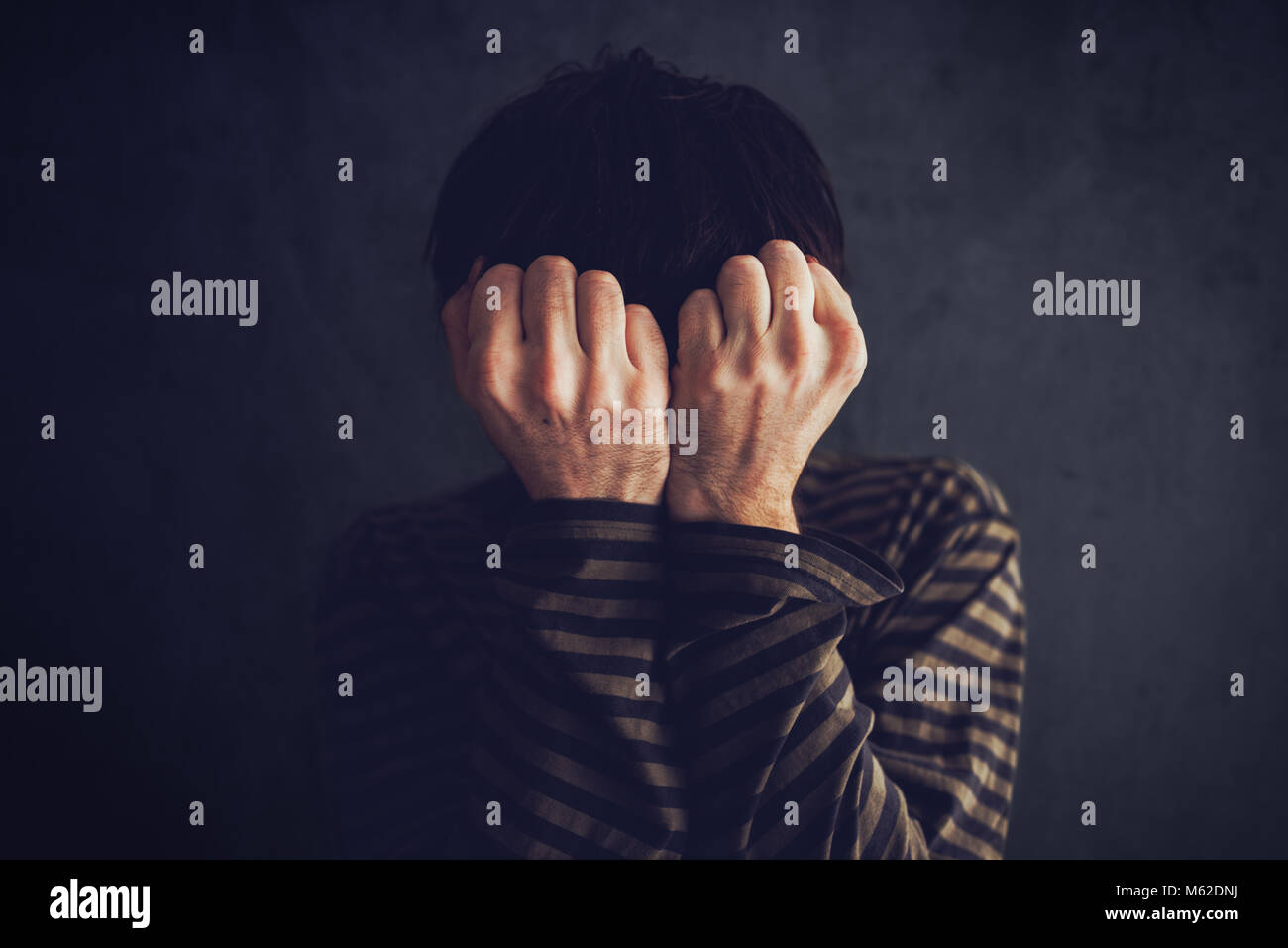 Distraught state of mind, depressive and sad man in dark room - Stock Image