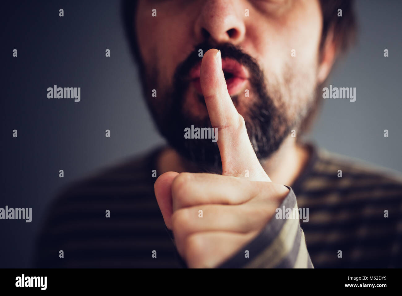 Man saying hush or be quiet with finger on lips, close up with selective focus - Stock Image