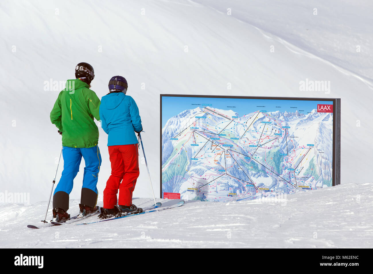 Couple view the ski map at Crap Masegn in Switzerland - Stock Image