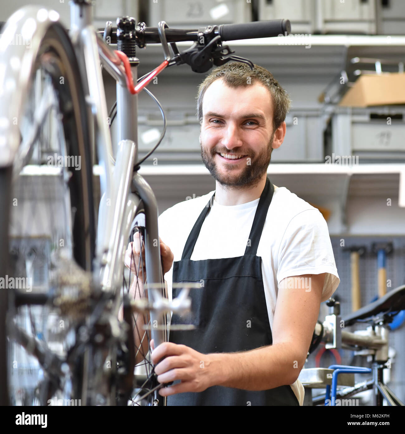 portrait of a friendly and competent bicycle mechanic in a workshop repairs a bike - Stock Image