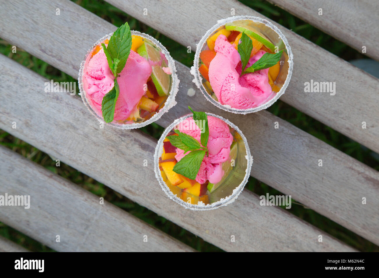 Three glasses with fruit salad and strawberry ice cream on the wooden surface. Top view Stock Photo