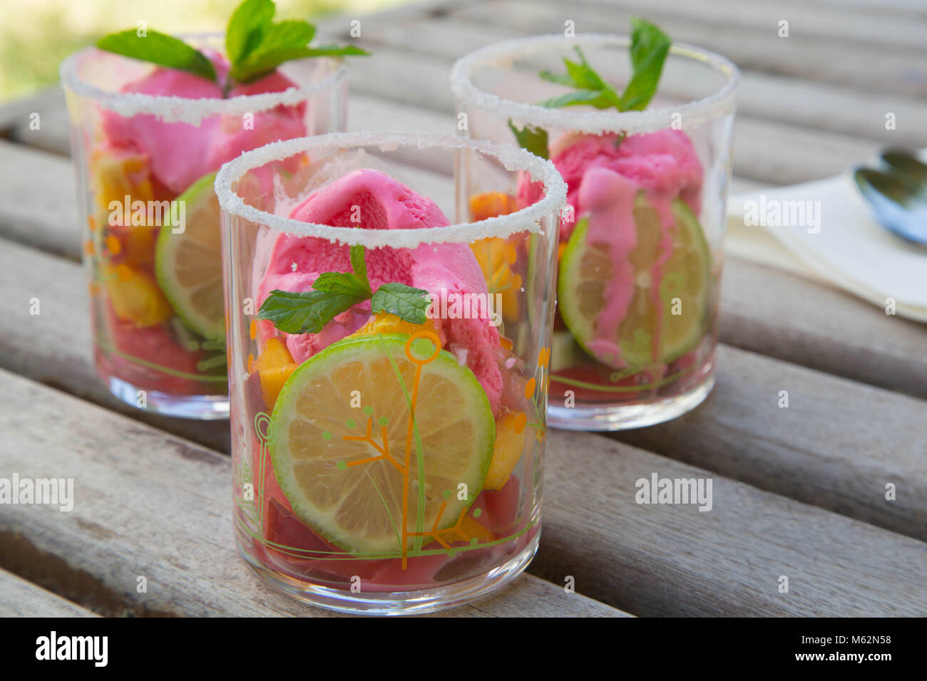 Three glasses with fruit salad and strawberry ice cream on the wooden surface. Spoons in the background Stock Photo