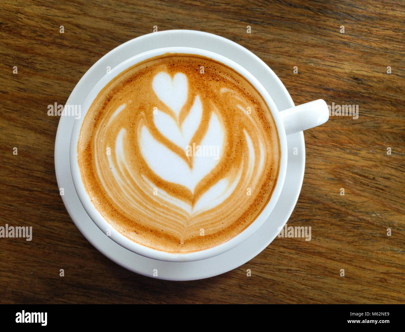 Delicious coffee cappuccino with white milk leaf decoration on white cup and plate over wooden background - Stock Image