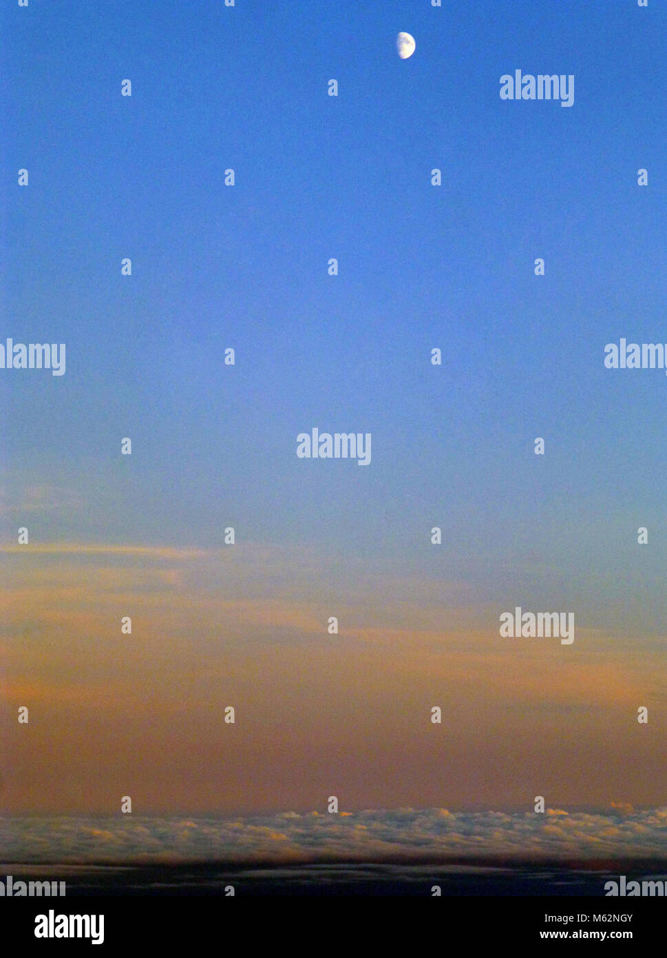 Aerial view of sunset sky with half moon - Stock Image
