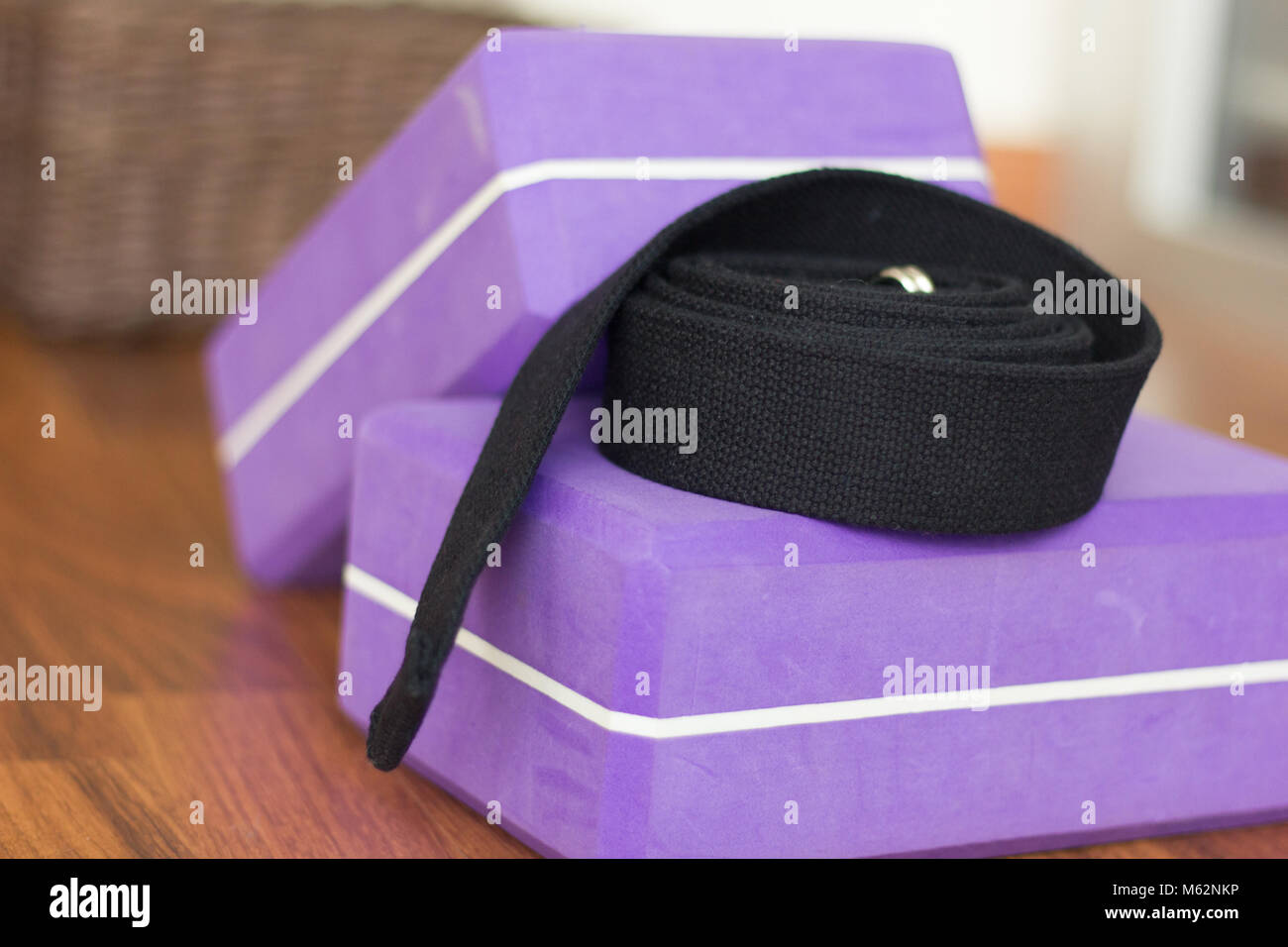 Close up on yoga purple blocks and black belt. Yoga studio material props - Stock Image