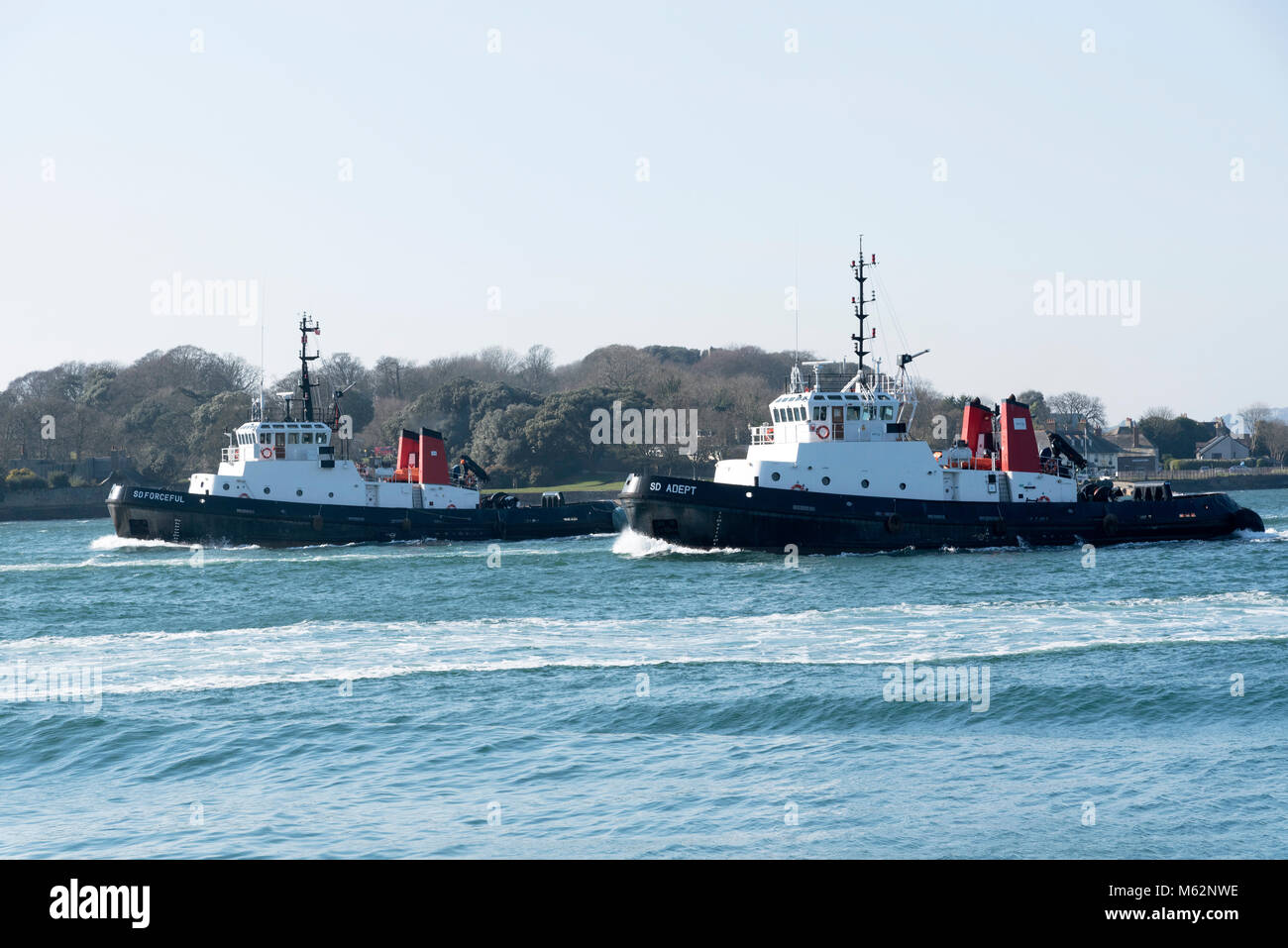 Plymouth, Devon, England, UK. Ocean going tugs SD Forceful and SD Adept underway departing Devonport Harbour. February - Stock Image