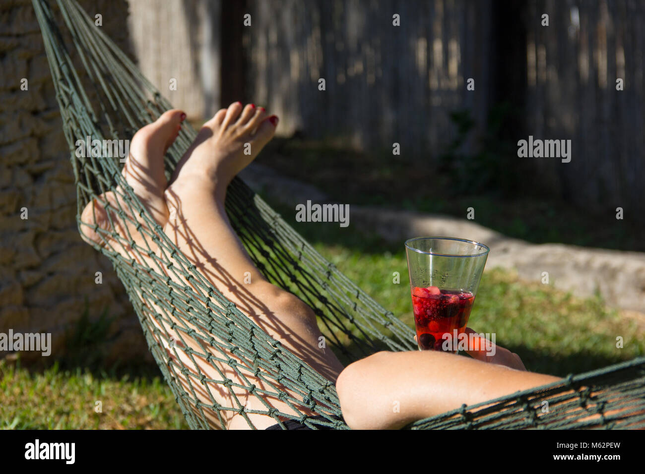 Woman on backyard net hammock chilling out holding cocktail