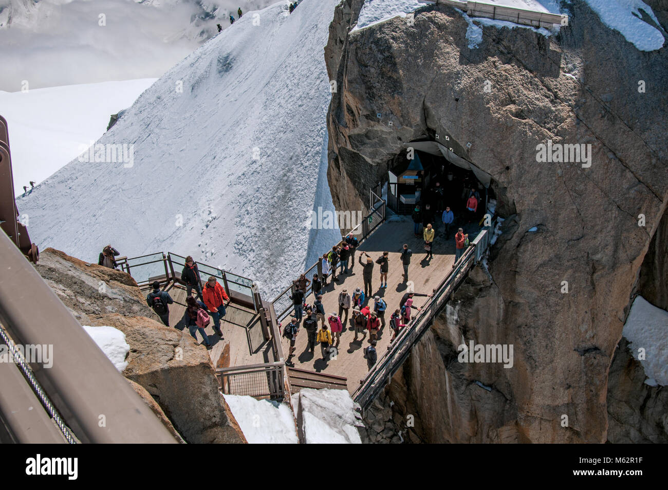 Footbridge between rocky peaks with tourists on the Aiguille du Midi, near Chamonix. A famous ski resort at the Stock Photo