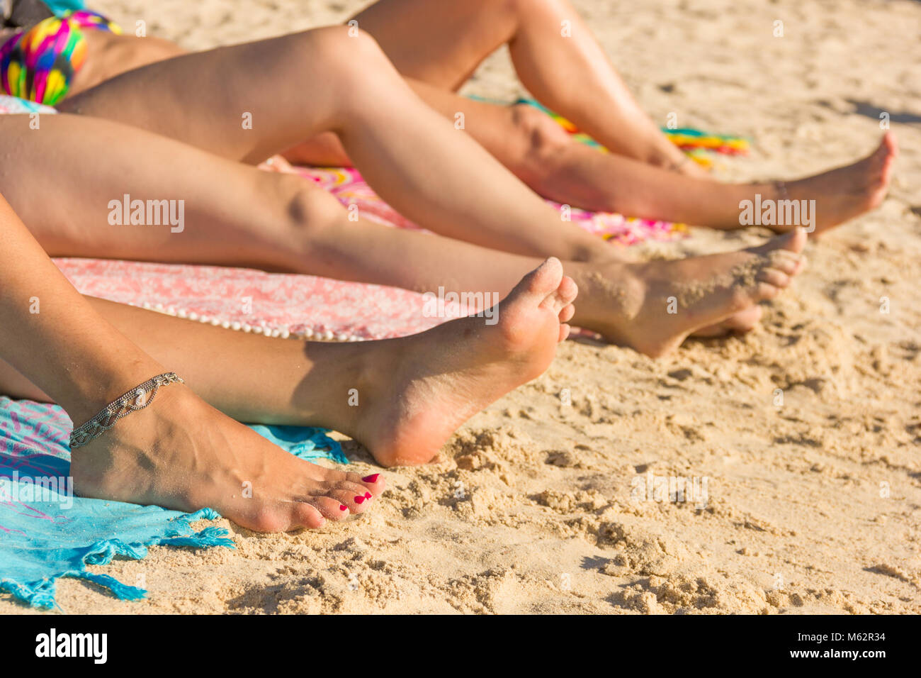 Feet and legs of three women sunbathing on the beach in the island of Koh Phangan, Thailand. Sun protection, summer - Stock Image