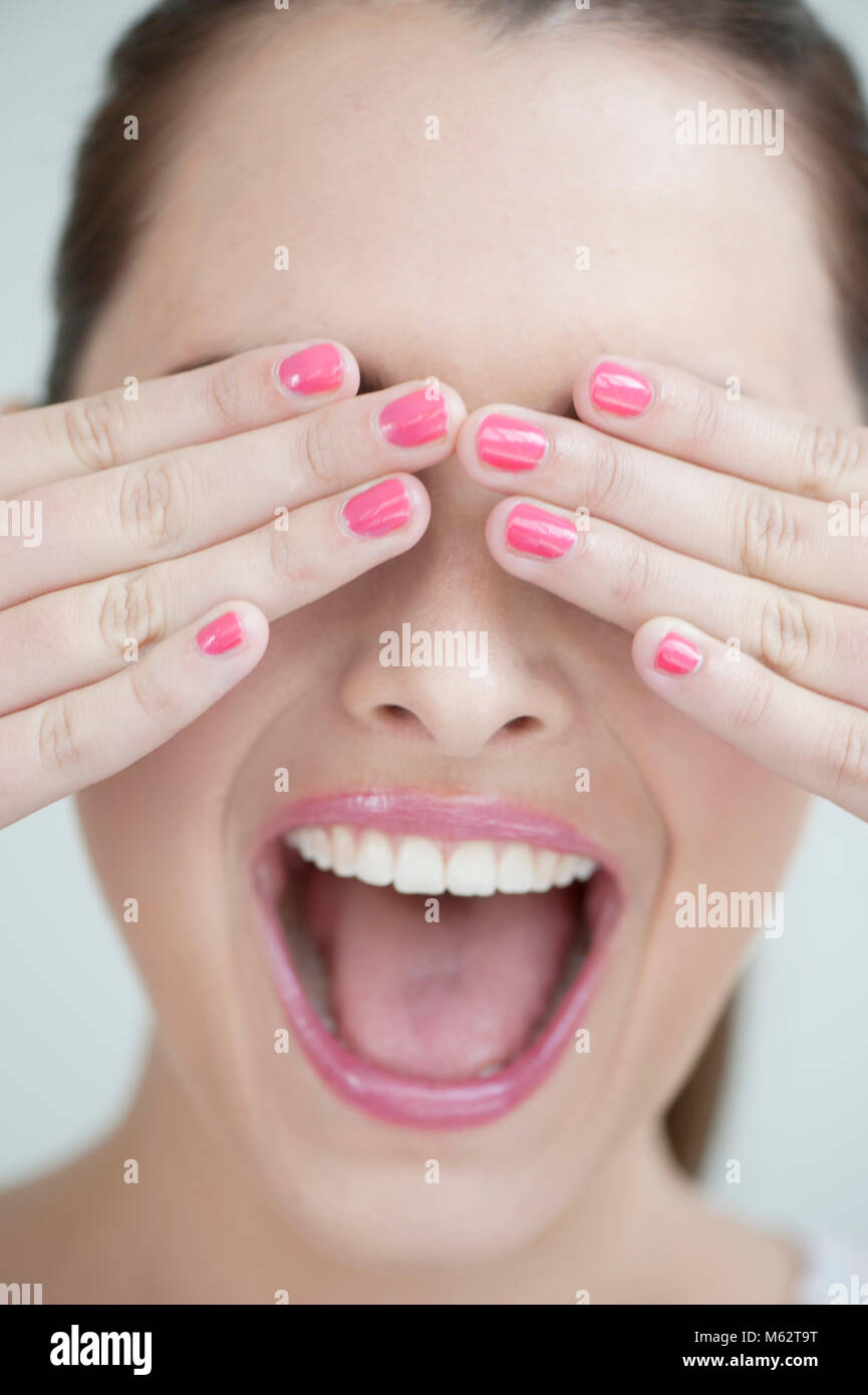 Laughing woman covering eyes with hands - Stock Image