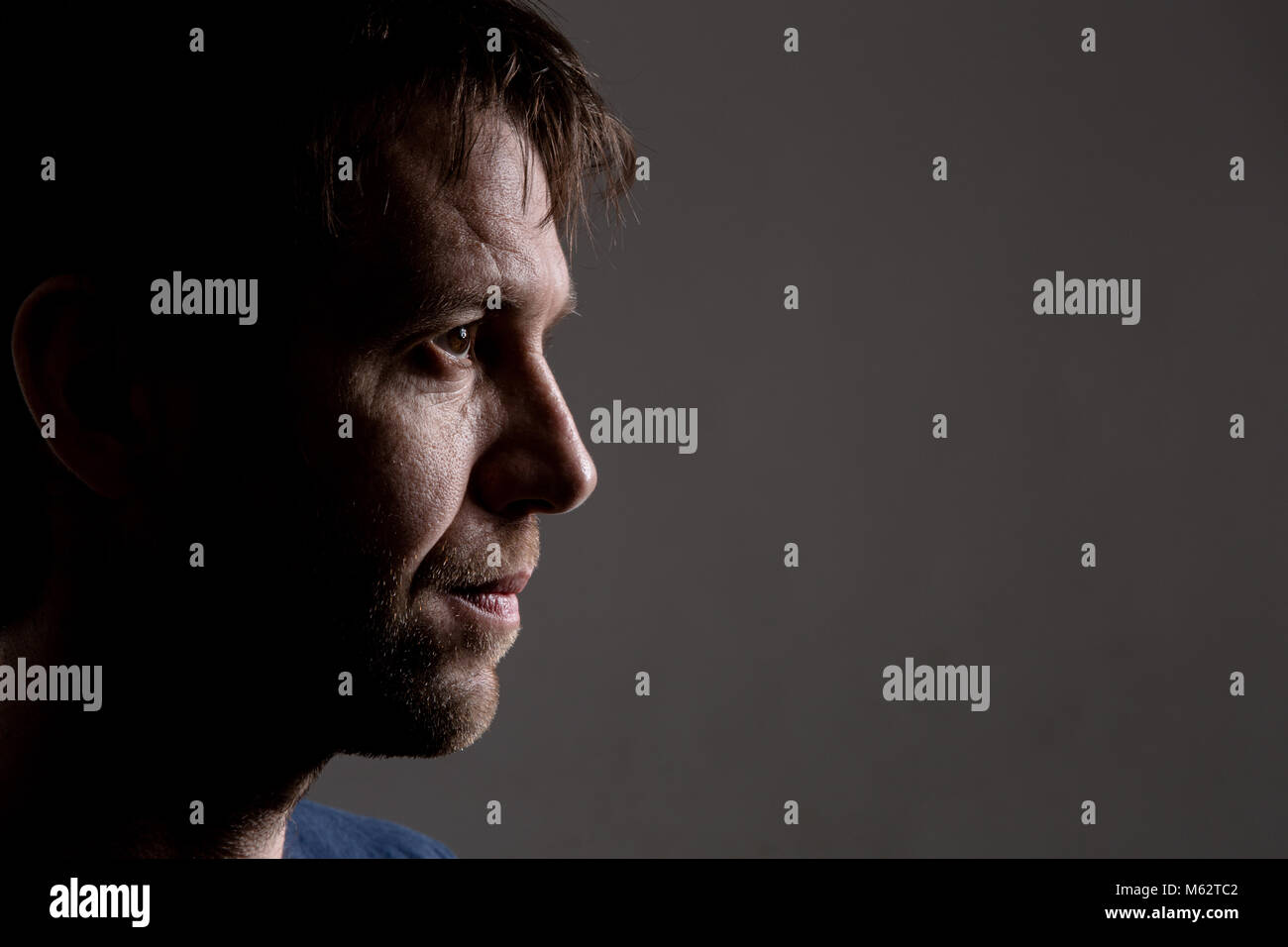 Young white male looking into frame with a thoughtful expression, plenty of copy space - Stock Image