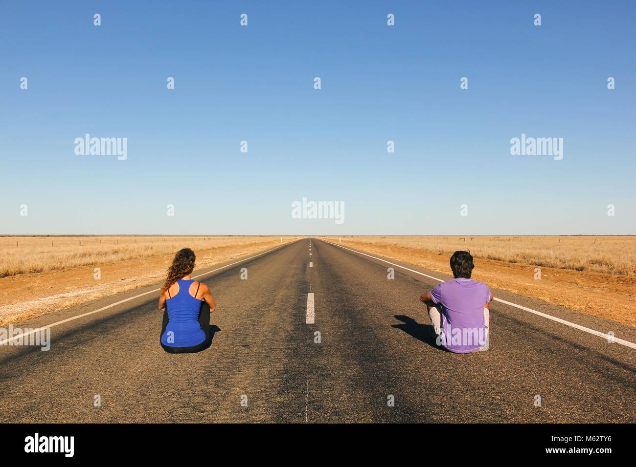 Young couple from behind sitting down on an endless straight empty road in the middle of nowhere in Outback Australia. Backpackers, visionary concept Stock Photo