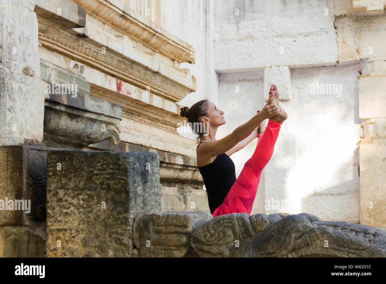 Yogi woman in upavistha konasana with pink leggings in Srirangapatna temple, Karnataka, India. Yoga teacher practicing Stock Photo