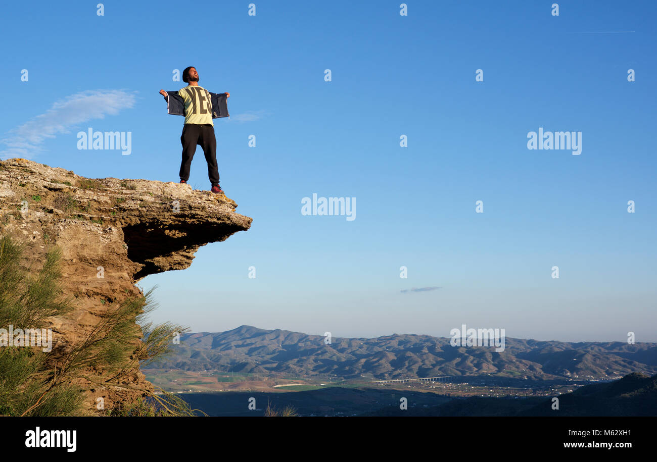 Man standing on top of a rocky outcrop showing a teeshirt which reads YES, and looking elated - Stock Image