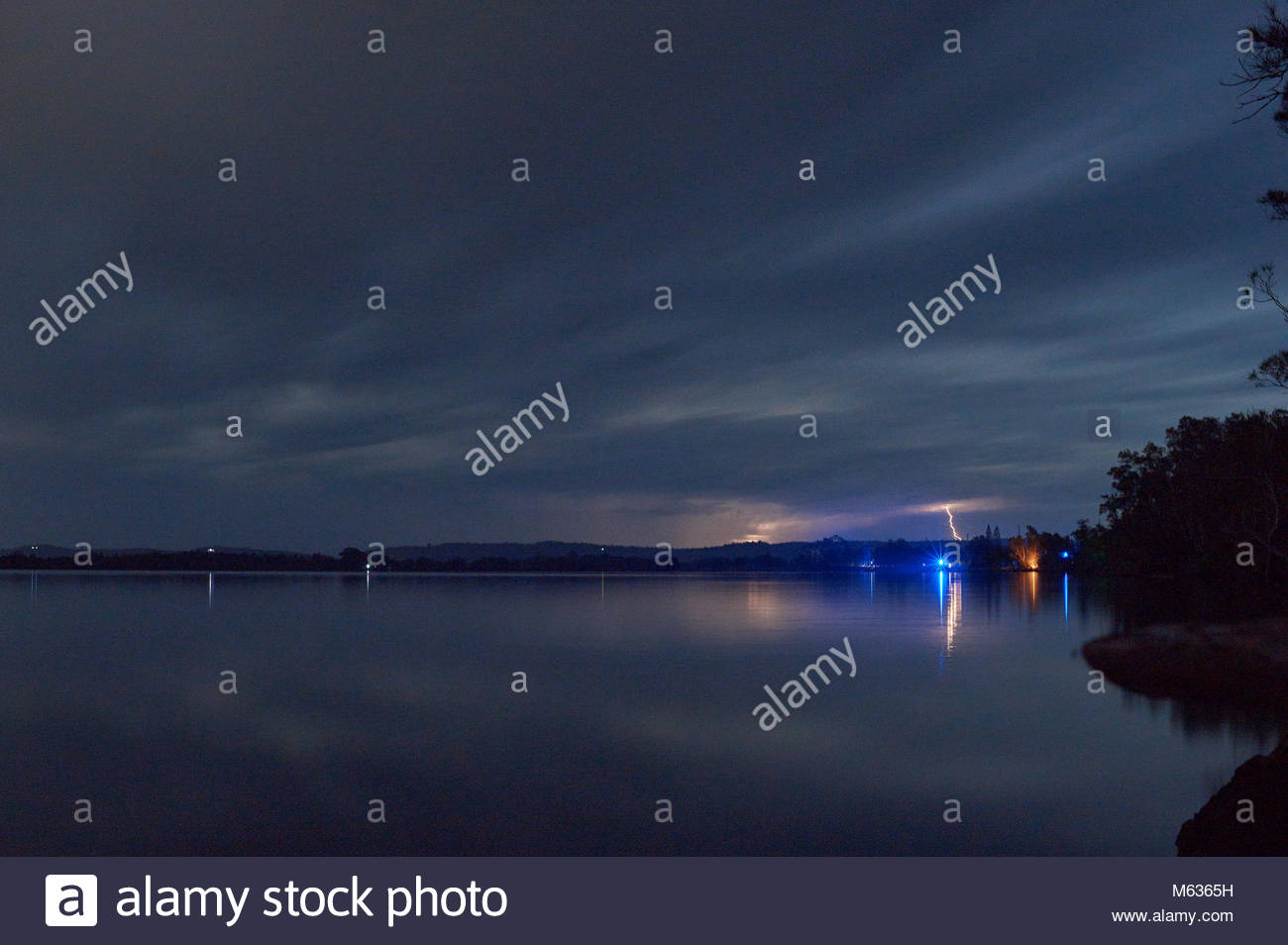 A long exposure image of dusk over the Clarence River, with a lightening storm in the distance; taken from Goodwood - Stock Image