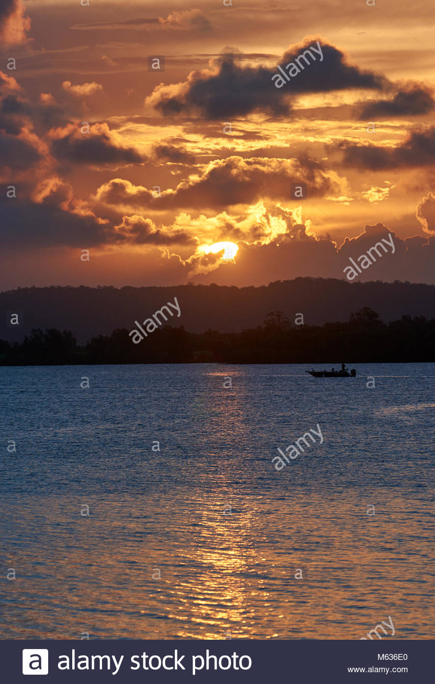 The colourful sky and water, of sunset over the Clarence River, with a fishing boat in the distance; taken near - Stock Image
