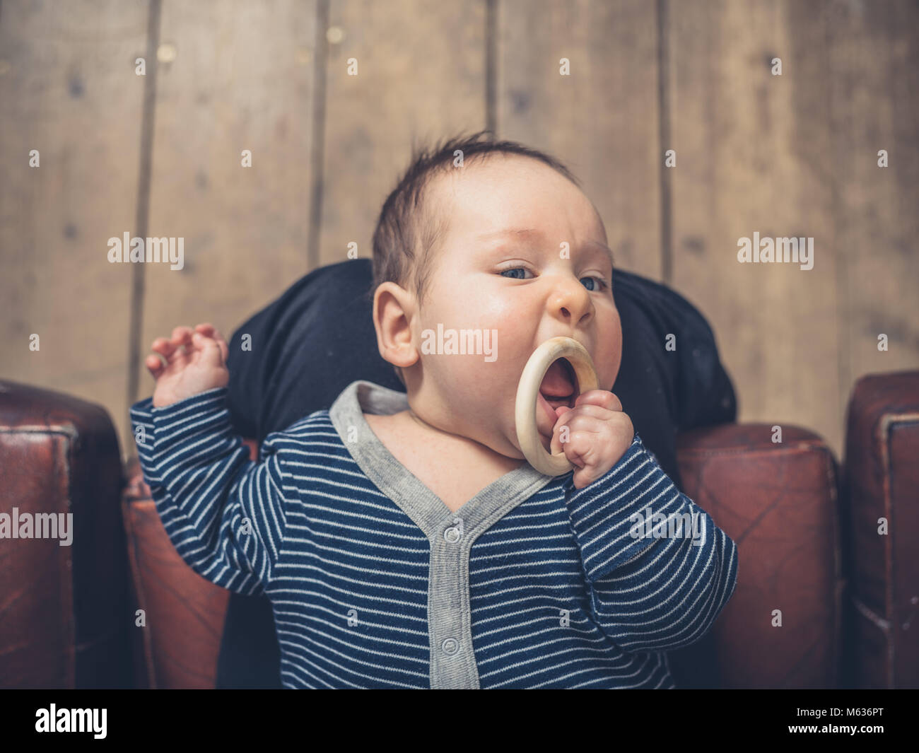 A little baby is chewing on a teething ring - Stock Image