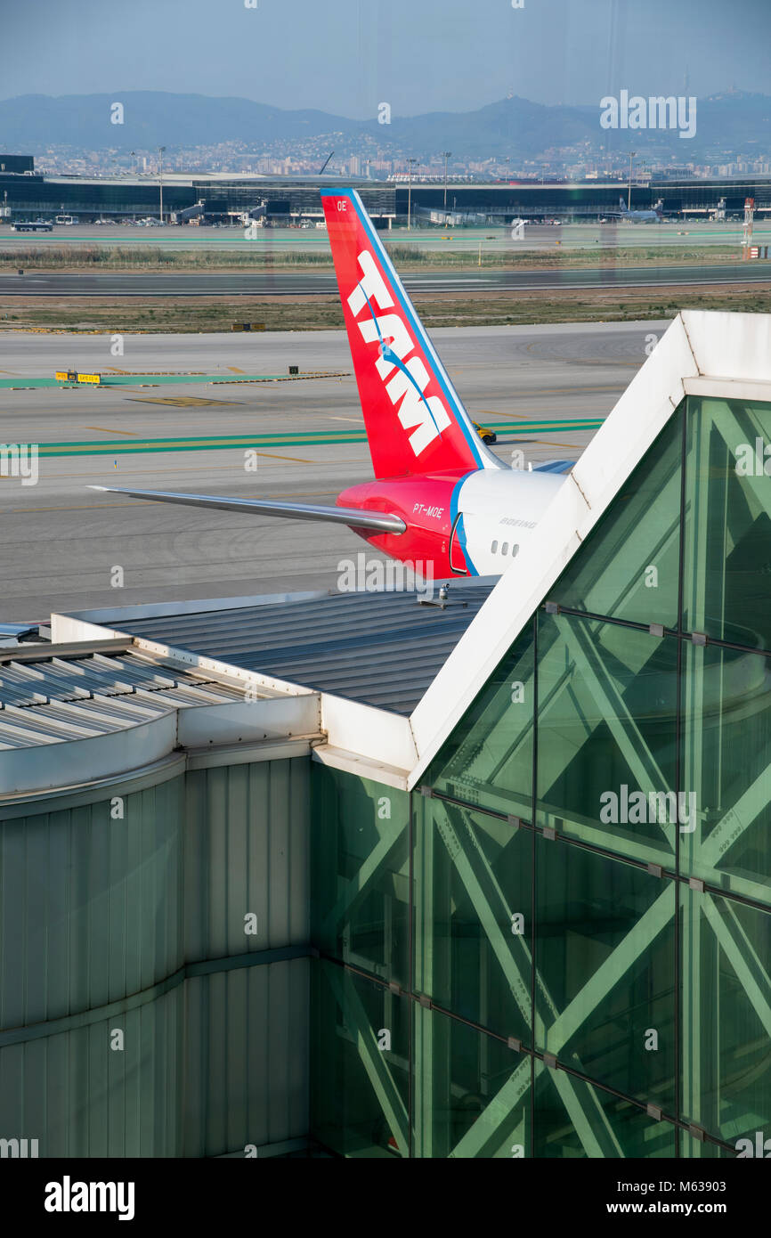 plane reflected in a terminal building while another airliner taxis past, Barcelona Airport Stock Photo